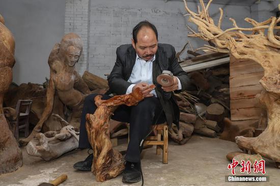 刘德付在工艺厂内打磨木雕作品。中新社记者 瞿宏伦 摄