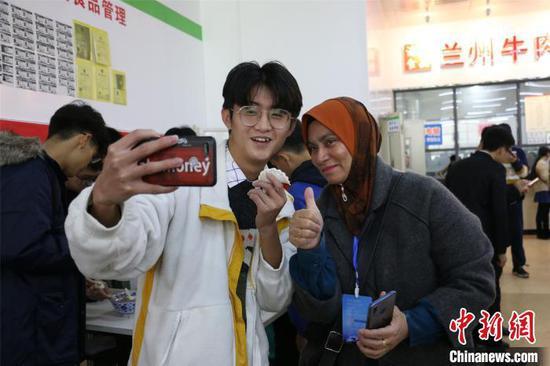 马来西亚教师与中国学生包饺子、合影。 林馨 摄