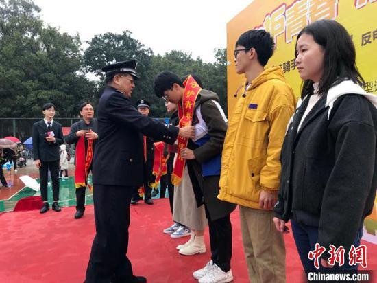 """出席启动仪式的嘉宾给外卖小哥及学生代表授""""反诈使者""""绶带。 蒋雪林 摄"""
