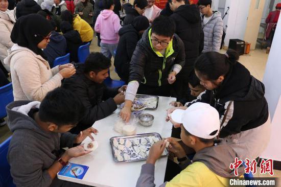22日,马来西亚33名师生在柳州铁道职业技术学院包饺子,过冬至。 林馨 摄