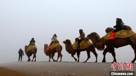 新疆库木塔格沙漠迎来入冬首场降雪