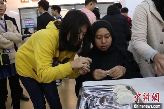图为中国学生教马来西亚学生包饺子。 林馨 摄