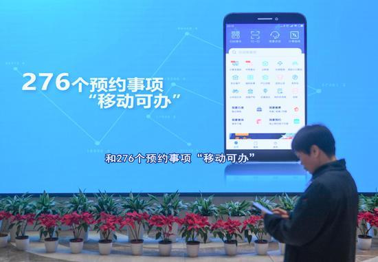 图为:一位市民从展示浙江杭州移动办事手机应用的屏幕前走过。   王刚 摄