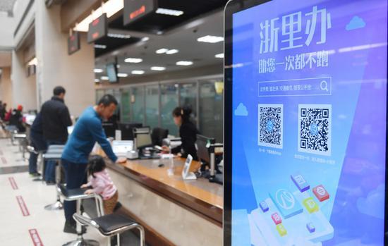 """图为:浙江杭州行政服务中心展示出民众办事""""最多跑一次""""的移动应用标识。  王刚 摄"""