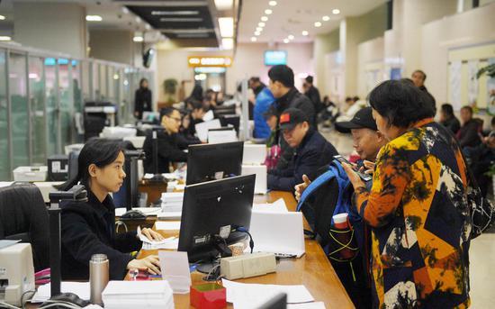 图为:多位市民在杭州行政服务中心办事。   王刚 摄