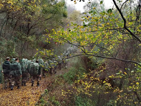 图为:寒冬,新战士们行走在山林茂密的山路上  章朝晖 摄