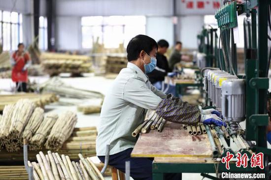 工人在给竹子钻眼。 朱柳融 摄