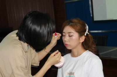 青年在美妆课堂学习化妆技巧。