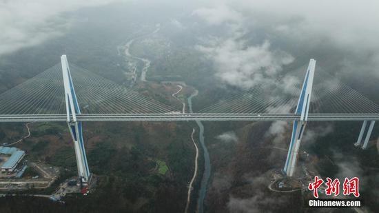 """12月30日,贵州平塘,世界第一混凝土高塔桥——平塘特大桥宣布建成通车,历时3年建设的贵州省平塘至罗甸高速公路也将全线贯通。据悉,平罗高速于2016年4月开工建设,平塘特大桥是其重大控制性工程,该桥全长2135米,是一座三塔双索面叠合梁斜拉桥,其中,16号""""钻石形""""主塔高达332米,相当于110层楼高,是目前世界最高钢筋混凝土桥塔。图为航拍平塘特大桥。中新社记者 瞿宏伦 摄"""