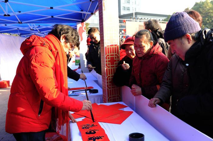 图为:一名书法家为市民书写春节对联。蔡自鑫摄