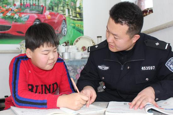 图一为民警正在帮助小女孩辅导功课。