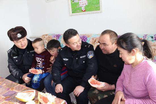 图二为民警们与阿曼古丽· 阿勒泰别克一家聊家常。