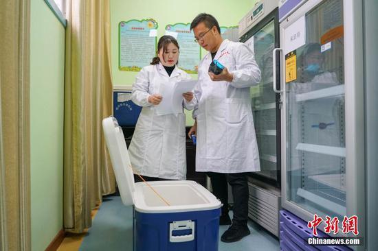 """1月3日,由贵州省疾控中心主办的""""疫苗出厂全流程追溯之旅""""活动在贵州省黔南州龙里县举行。贵州省已实施疫苗数字化监控系统项目,已经实现辖区内疫苗的全程电子追溯,疫苗全程温度自动监控报警。据了解,此次疫苗数字化监控系统覆盖了贵州省疾控中心、9个市州、88个县(市区)疾控中心,1579个预防接种单位。图为龙里县冠山街道社区卫生服务中心工作人员核对疫苗出库单。中新社记者 瞿宏伦 摄"""