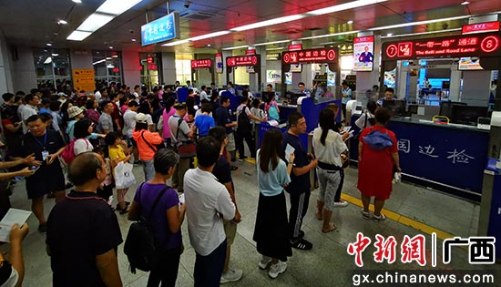 图为旅客排队接受入境边防检查 。林珉正摄