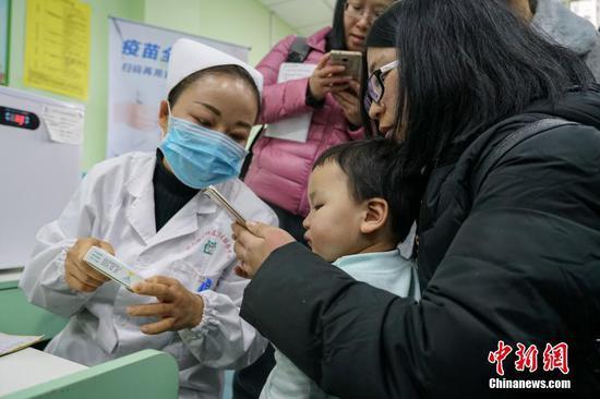 """1月3日,由贵州省疾控中心主办的""""疫苗出厂全流程追溯之旅""""活动在贵州省黔南州龙里县举行。贵州省已实施疫苗数字化监控系统项目,已经实现辖区内疫苗的全程电子追溯,疫苗全程温度自动监控报警。据了解,此次疫苗数字化监控系统覆盖了贵州省疾控中心、9个市州、88个县(市区)疾控中心,1579个预防接种单位。图为龙里县冠山街道社区卫生服务中心护士指导儿童家长用手机查询疫苗信息。中新社记者 瞿宏伦 摄"""