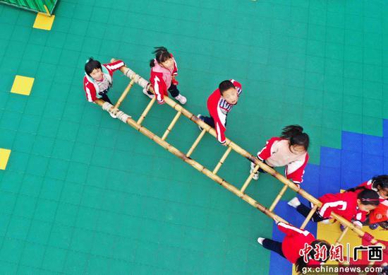 孩子们和老师在户外做游戏。谭凯兴 摄