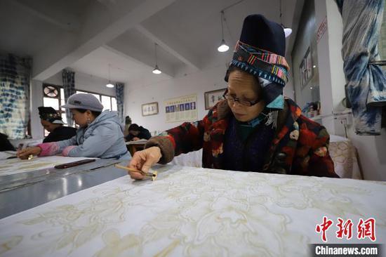贵州丹寨宁航蜡染传承基地,苗族画娘在画蜡染床单。 黄晓海 摄