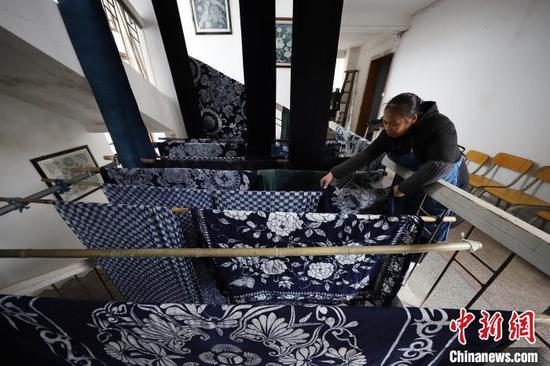 贵州丹寨宁航蜡染传承基地,一名工人在晾晒染好的蜡染床单。 黄晓海 摄