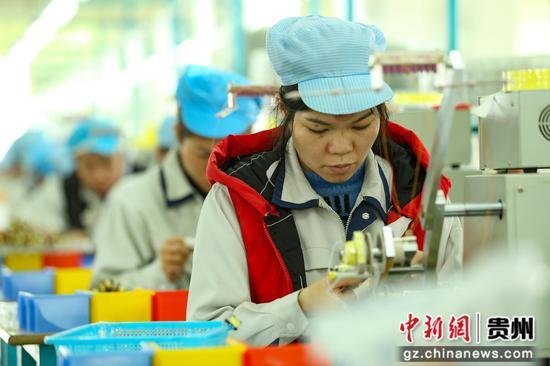 """圖為貴州省丹寨縣""""扶貧微工廠""""瑪司特公司電子加工車間里,工人在微型變壓器生產線上忙碌。  黃曉海"""