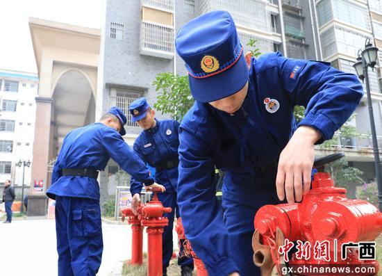 消防人員查看消防栓保養情況。韋榮軍 攝