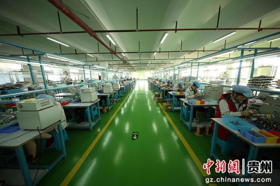 """圖為貴州省丹寨縣""""扶貧微工廠""""瑪司特公司電子加工車間里,工人在微型變壓器生產線上忙碌。  黃曉海 攝"""
