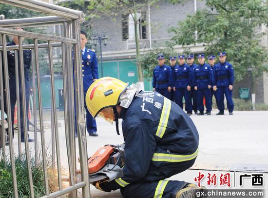 消防人員對占用消防車通道的崗亭圍欄進行現場拆除。韋榮軍 攝