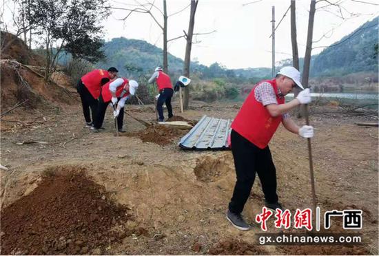 图为志愿者为鸡场扩建挖坑打桩。