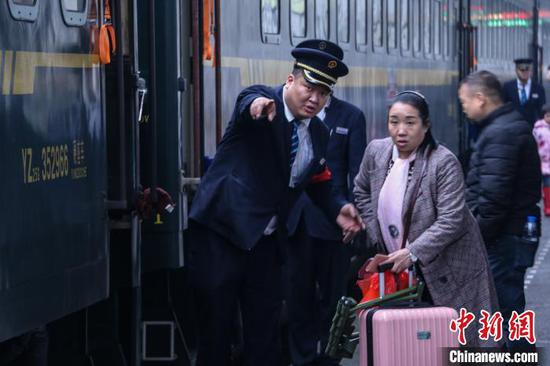 图为乘务员在帮助旅客。 王东铃 摄