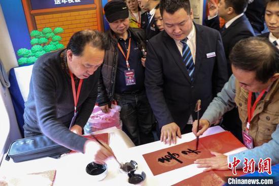 图为工作人员在列车上写春联。 王东铃 摄
