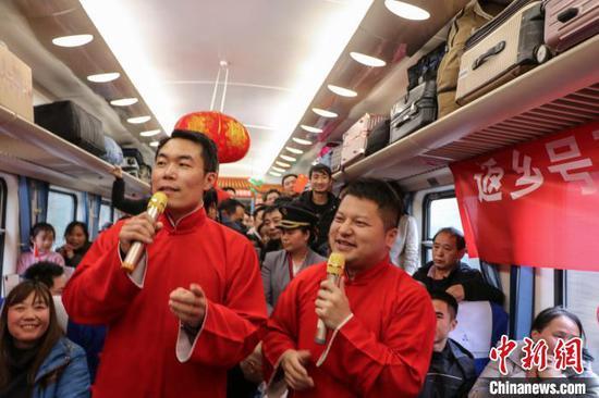 图为工作人员在列车上表演相声节目。 王东铃 摄