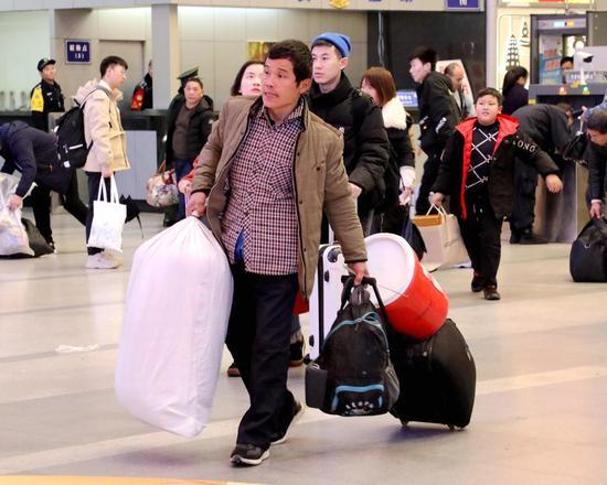 图为:一位旅客带着大量行囊赶车。  柱子(通讯员) 摄