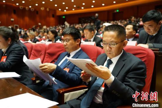图为参会代表认真阅读《政府工作报告》。 瞿宏伦 摄