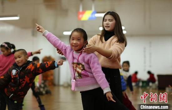 """貴州丹寨金鐘易地扶貧搬遷安置區""""4點半學堂"""",志愿者在糾正孩子們的舞蹈動作?!↑S曉海 攝"""