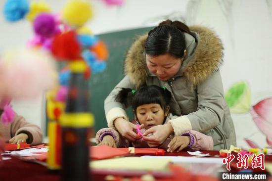 """貴州丹寨金鐘易地扶貧搬遷安置區""""4點半學堂"""",志愿者在教一名小孩子做新年賀卡?!↑S曉海 攝"""