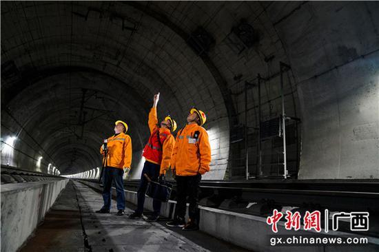 铁路职工正在对隧道进行检查。 伍汉 摄