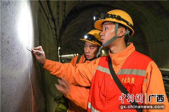 铁路职工正在用小钢尺测量施工缝宽度。伍汉 摄