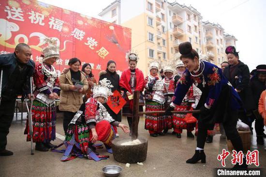 安置點的居民們在表演苗族過年民俗:打粑粑。 黃曉海 攝