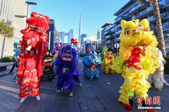 """当地时间1月17日,中国大学生体育协会舞龙舞狮分会的大学生们在迪拜街头舞狮。当日,迪拜举行2020""""欢乐春节""""大巡游,迎接即将到来的中国农历新年。 杨华峰 摄"""
