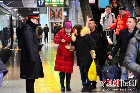 圖為凌晨2時杭州站站臺上,列車長牛鮮鮮正在引導旅客上車。 胡威 攝