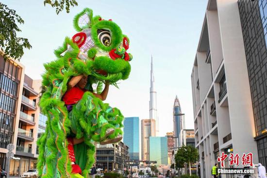 """当地时间1月17日,巡游队伍中一头狮子高高跃起。当日,迪拜举行2020""""欢乐春节""""大巡游,迎接即将到来的中国农历新年。 杨华峰 摄"""