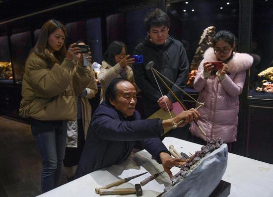 图为:中新社浙江分社记者记录青田石雕传承人张爱光创作。  王刚 摄