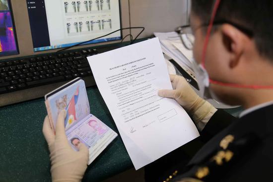 圖為海關關員驗核健康申明卡。寧波海關供圖