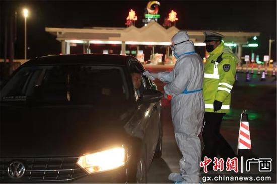 防疫人员对过往车辆人员身体情况进行排查 。