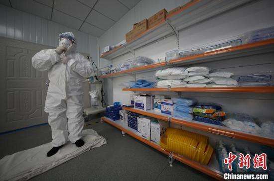 图为李斌在穿防护服准备到隔离病房巡诊。 黄晓海 摄