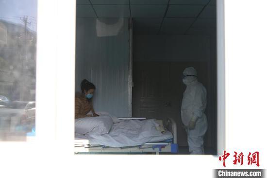 图为李斌在隔离病房向患者了解病情。 黄晓海 摄