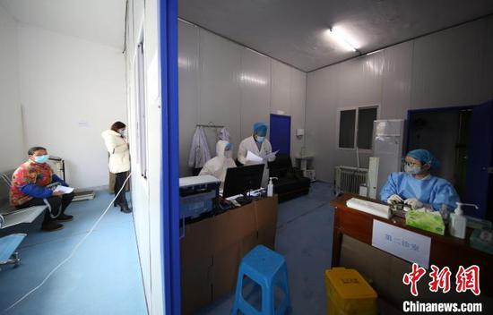 图为李斌(右二)和同事讨论病人的情况。 黄晓海 摄