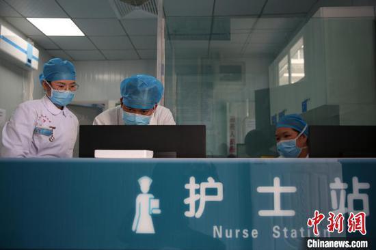 图为李斌(中)在和同事讨论病人的康复状况。 黄晓海 摄