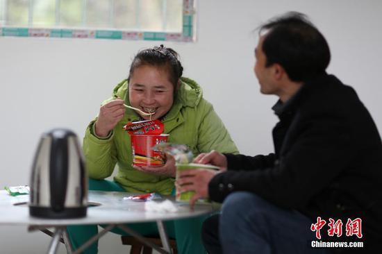 图为1月31日,肖世军(右)、潘启兰吃泡面充饥。 中新社发 黄晓海 摄