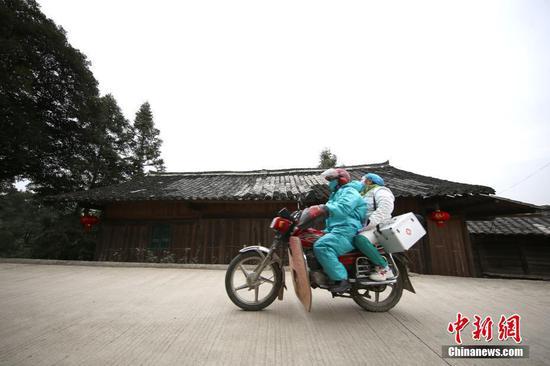 图为1月31日,肖世军(蓝衣)、潘启兰在巡诊途中。中新社发 黄晓海 摄