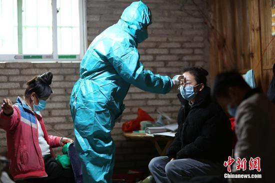 图为1月31日,肖世军为返乡村民测量体温。 中新社发 黄晓海 摄